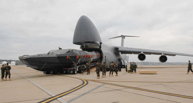 Here the C-5 unloads an 81-foot boat for the Navy.