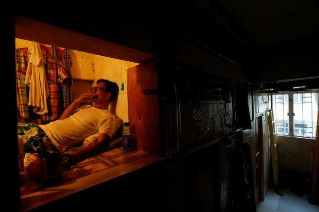 "Simon Wong, an unemployed 61-year-old man also living in Hong Kong, lives in a 4'x6' box. He's one of many residents living in so-called ""coffin homes."""