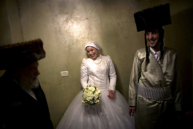 In keeping with the Jewish tradition of modesty, the ultra-Orthodox bride wears a loose-fitting gown that covers everything but her face and hands. A lacy skirt grazes the floor.