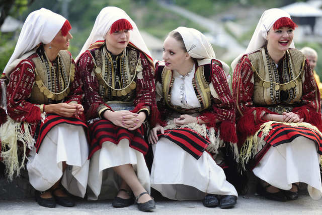 In a traditional wedding in Macedonia, the bride wears an intricately embroidered smock in red, white, and gold.