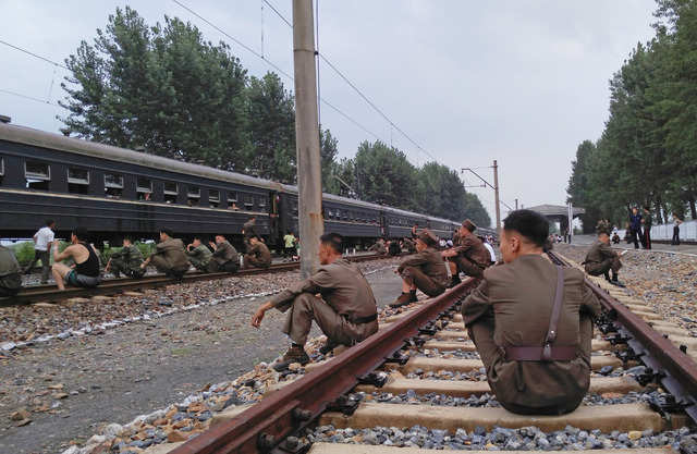 Korean People's Army soldiers rested on the tracks.