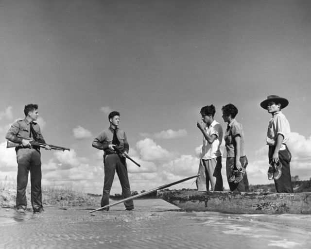In this 1948 photo, two armed American border guards deterred a group of undocumented immigrants from crossing a river into the US.