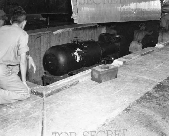 The tarp is removed and the bomb is readied for loading.