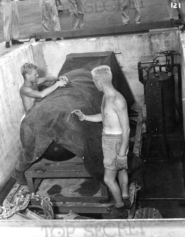 """Workers check """"Little Boy"""" one last time, keeping the tarp on for security reasons, following a lowering procedure similar to the one done for """"Fat Man"""" three days later."""