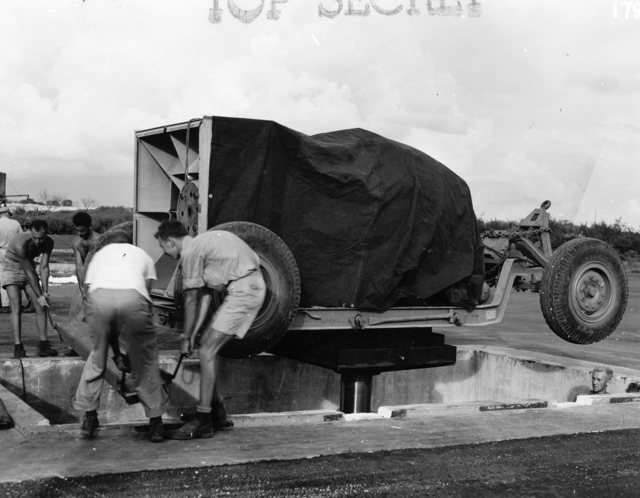 The bomb and its trailer are lowered down into the pit using a hydraulic lift.