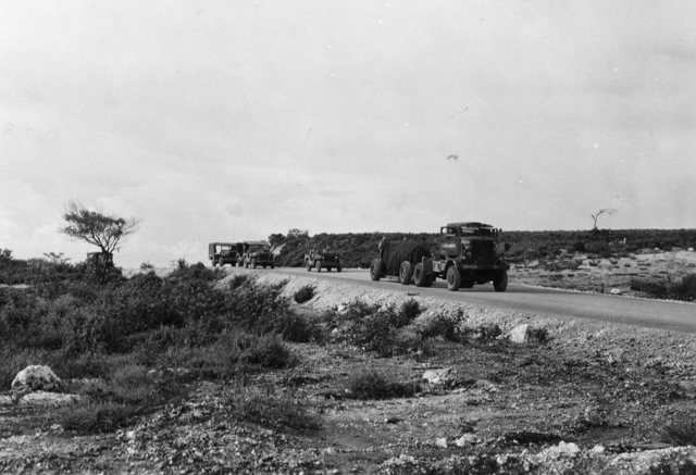 The bomb is then escorted to the nearby North Field airbase on Tinian, shrouded by a tarp.