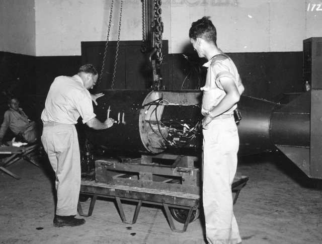 """On the left, geophysicist and Manhattan Project participant Francis Birch marks the bomb unit that would become """"Little Boy,"""" while Norman Ramsey, who would later win the Nobel Prize in physics, looks on."""