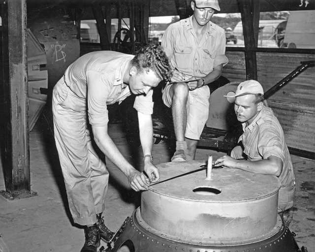 """Soldiers check the casings on the """"Fat Man"""" atomic bomb. Multiple test bombs were created on Tinian Island. All were roughly identical to an operational bomb, even though they lacked the necessary equipment to detonate."""