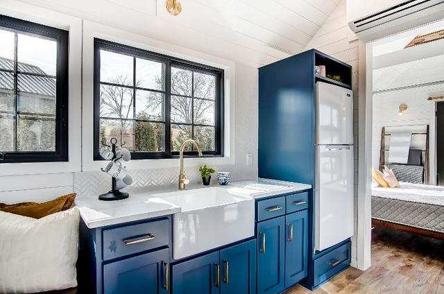 The home's kitchen includes a farmhouse sink and sizable refrigerator.