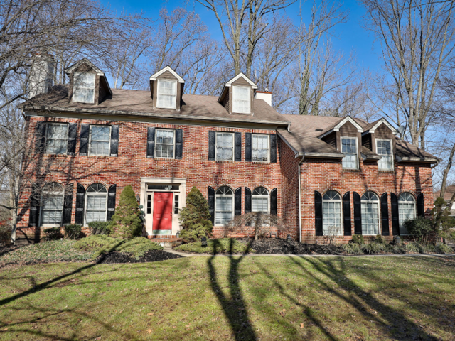 You've got your typical colonial-style, two-story house with a red brick exterior.