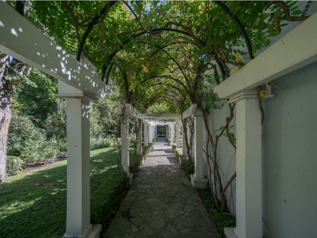 Outside, an arched walkway leads through the manicured lawn, and private hiking trails wind through the property.