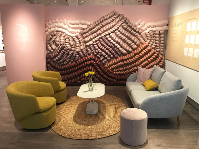 The store includes a lounge area near the front where shoppers can wait to chat with a fit stylist from beneath a wall made entirely of bras.