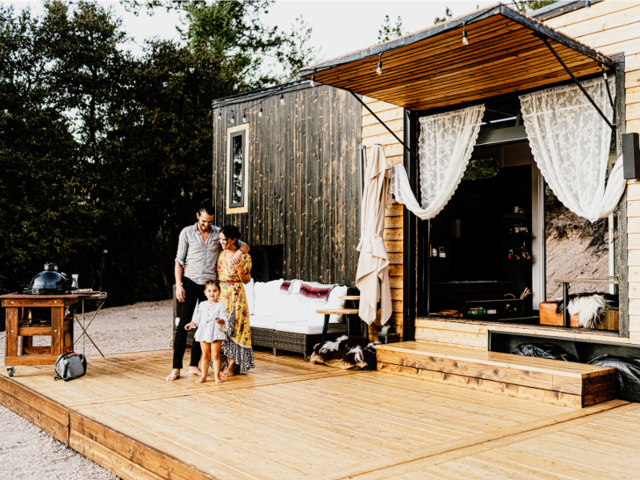 Couple Bela and Spencer cut their housing costs in half when they downsized to a tiny home — and they earn income of it by turning their tiny house into a vacation rental.