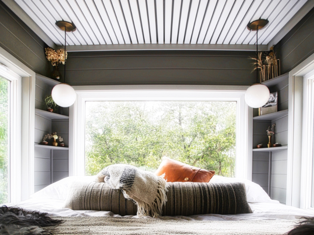 "They put their master bedroom over the tiny house's fifth wheel hitch, which gives them full standing room. A giant picture window ""opens it to the outdoors and makes it feel expansive."""